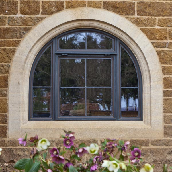 curved bronze window in a stone mullion