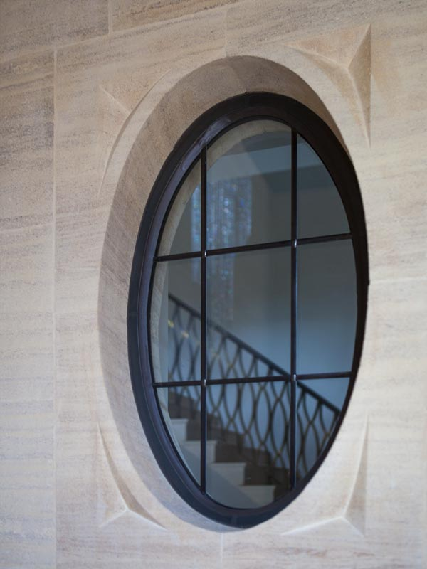 oval curved metal window with vertical and horizontal transoms