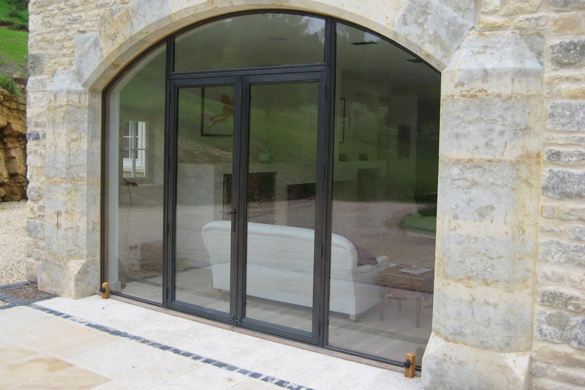 curved glass in a simple bronze screen