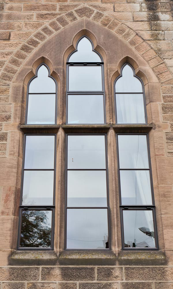 shaped metal windows in stone surrounds